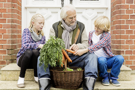 Grandfather sitting with grandchildren on doorstep with carrots LANG_EVOIMAGES
