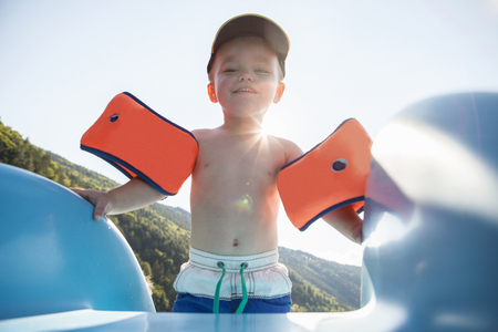 armbands: Boy wearing armbands at top of water slide LANG_EVOIMAGES