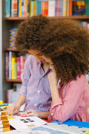 Brother and sister browsing design book in library