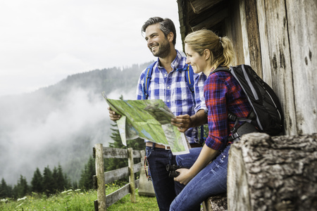Couple with map embarking on trek,Tirol,Austria LANG_EVOIMAGES
