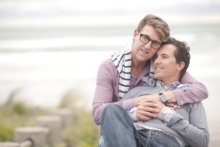 Gay couple hugging on beach