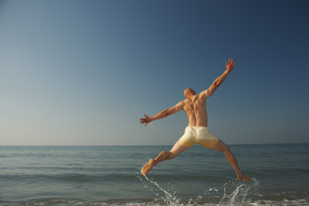 legs around: Mid adult man jumping outstretched over sea