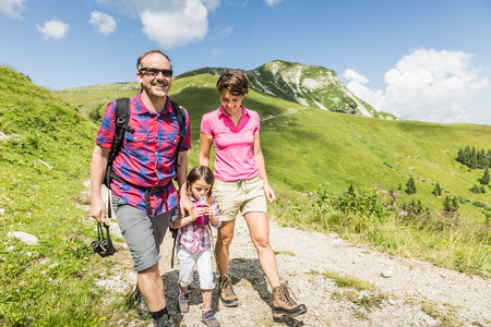 Parents and daughter walking on mountain track,Tyrol,Austria