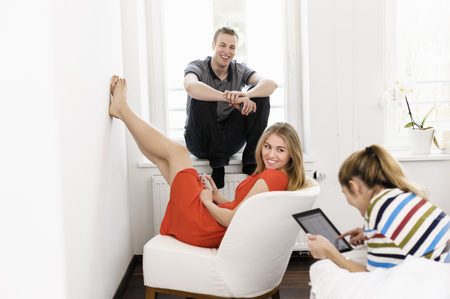 Three young adult friends lounging in bedroom