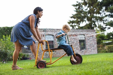3 4 years: Mother pushing son on tricycle LANG_EVOIMAGES