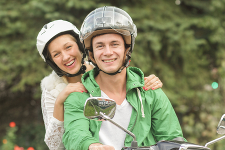 Portrait of young couple in helmets sitting on vespa