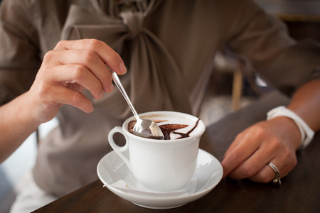 Close up of female hand stirring cappuccino LANG_EVOIMAGES