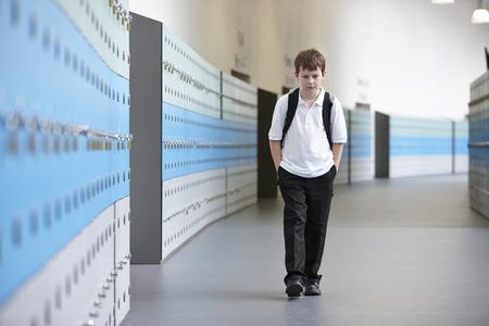 insecurity: Unhappy schoolboy walking alone in school corridor LANG_EVOIMAGES