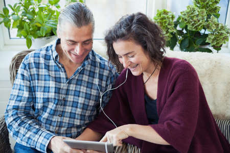 conservatories: Mature couple listening to music on digital pad