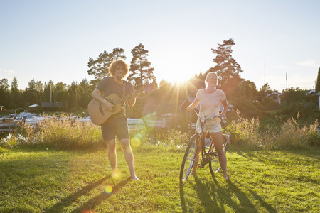 Young couple with guitar and bicycle,Gavle,Sweden LANG_EVOIMAGES