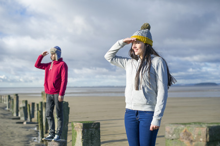 Young couple standing on groynes,Brean Sands,Somerset,England