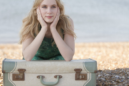 Portrait of young woman with suitcase on beach,Whitstable,Kent,UK LANG_EVOIMAGES