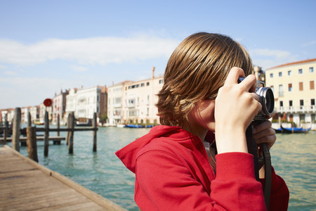 Young boy taking photographs on camera,Venice, Italy