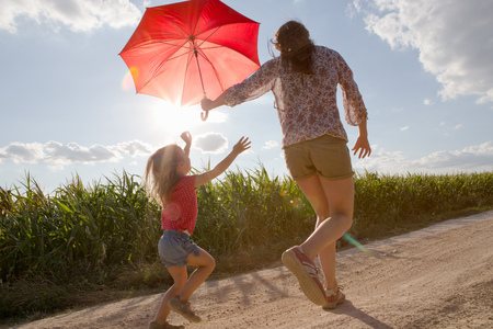 3 4 years: Mother and daughter walking through field carrying red umbrella