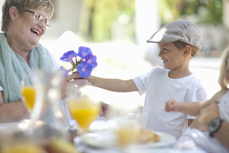 Boy giving flowers to grandmother