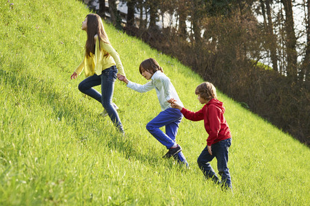 Sister and younger brothers climbing up grassy field LANG_EVOIMAGES