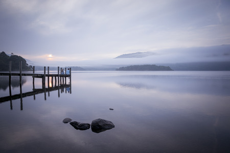 cumbria: Couple on pier by tranquil lake,Cumbria,England,UK LANG_EVOIMAGES