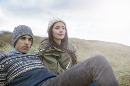 brean: Young couple sitting on beach,Brean Sands,Somerset,England LANG_EVOIMAGES