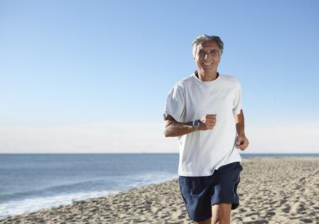 65 69 years: Senior man jogging on beach
