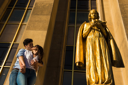 Young couple sharing a kiss next to statue, Paris, France