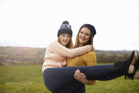 Teenage girl being lifted up by best friend