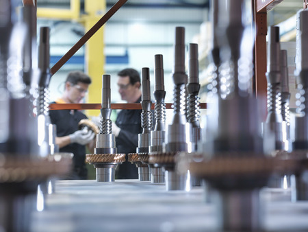 Engineers with parts in industrial gearbox factory