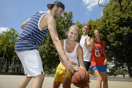 25 35: Group of friends playing basketball in park