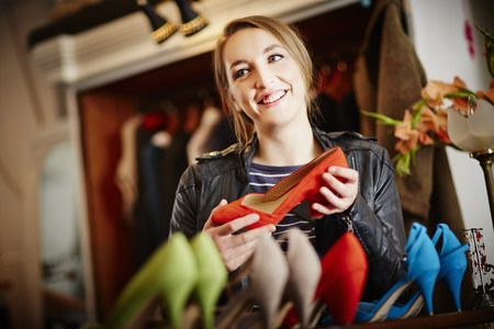 Young woman looking at selection of high heeled shoes LANG_EVOIMAGES