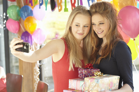 Two teenage girls taking selfie at birthday party LANG_EVOIMAGES