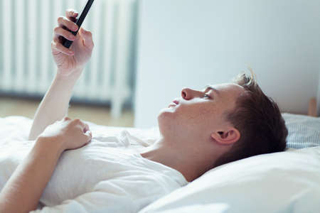 information superhighway: Young man lying in bed using mobile phone LANG_EVOIMAGES