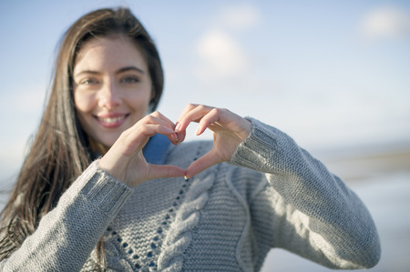 brean: Young woman making heart shape with hands LANG_EVOIMAGES