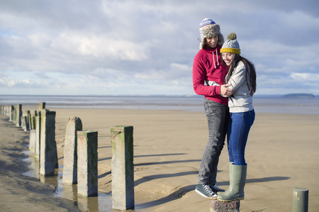 groynes: Young couple standing on groynes,Brean Sands,Somerset,England