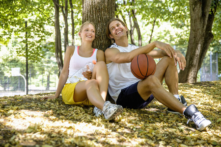 Basketball couple taking a break in park LANG_EVOIMAGES