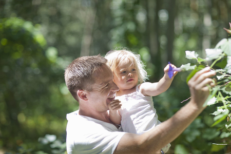 Father with baby girl plucking flowers in forest
