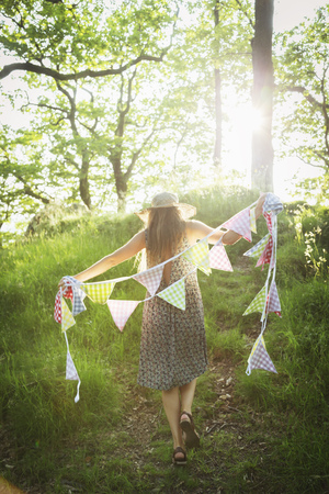 cumbria: Young woman walking with bunting in forest