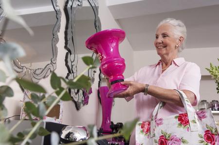 Senior woman holding up vase in florist shop
