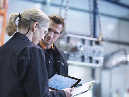 Engineers inspect plans on digital tablet in engineering factory LANG_EVOIMAGES
