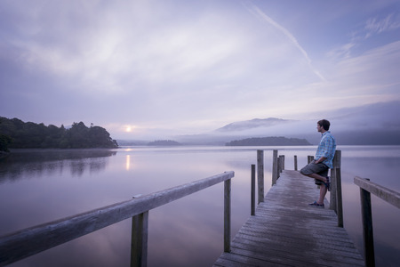 Man on pier by tranquil lake,Cumbria,England,UK