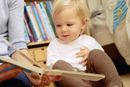 Mother reading picture book with baby daughter LANG_EVOIMAGES