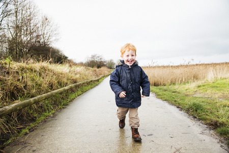 Male toddler running along rural road