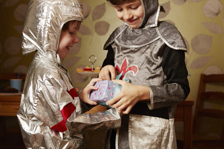 7 8: Two boys dressed as knights, one receiving birthday present