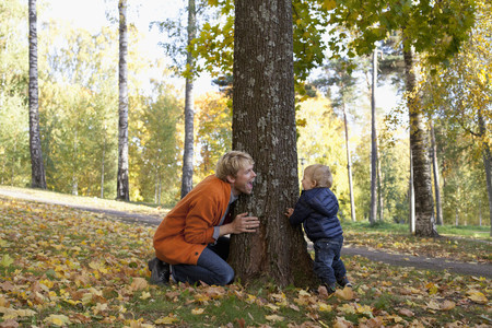 Father and son playing at bottom of tree