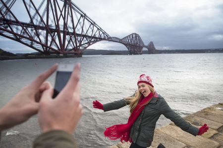 A young couple pose in front of the Forth Rail Bridge in Queensferry, near Edinburgh, Scotland