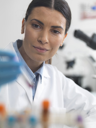 Female scientist about to view a sample under a microscope