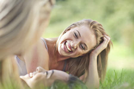Three young females friends lying in grass LANG_EVOIMAGES