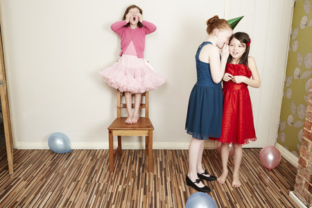 Three girls playing hide and seek at birthday party