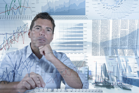 Businessman working with graphs and charts seen through screen LANG_EVOIMAGES