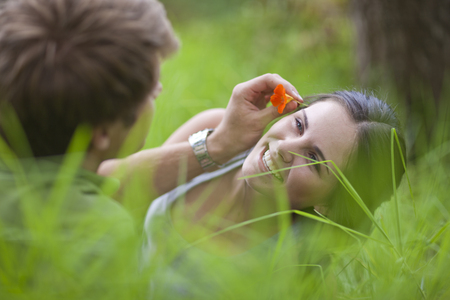 Young man putting flower in womans hair LANG_EVOIMAGES