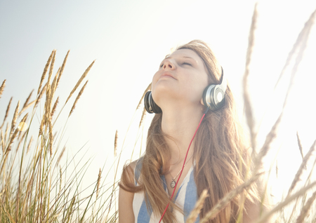 Teenage girl listening to music outdoors