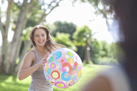 Two young females friends playing with a beach ball